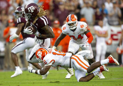 FILE - In this Saturday, Sept. 8, 2018, file photo, Texas A&M wide receiver Kendrick Rogers (13) breaks a tackle by Clemson defensive back K'Von Wallace (12) after a reception in the first half of an NCAA college football game, in College Station, Texas. The Tigers have questions to answer about their dominant defense, which gave up 501 yards and three second-half touchdowns in Texas A&M's rally in a 28-26 loss. (AP Photo/Sam Craft, File)