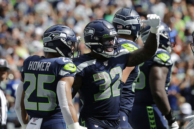 Seattle Seahawks running back Chris Carson (32) celebrates with running back Travis Homer (25) after Carson scored a touchdown during the first half of an NFL football game, Sunday, Sept. 8, 2019, in Seattle. (AP Photo/John Froschauer)