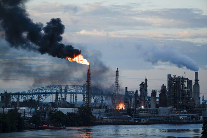 FILE - In this June 21, 2019 file photo, flames and smoke emerge from the Philadelphia Energy Solutions Refining Complex in Philadelphia. Federal investigators say an aging, failed elbow pipe appears to be the cause of the June fire and subsequent explosions that left five people with minor injuries and destroyed part of the processing unit at the largest oil refinery on the East Coast. The U.S. Chemical Safety and Hazard Investigation Board released a preliminary report Wednesday, Oct. 16 on findings from the June 21 explosion at the Philadelphia Energy Solutions Refining Complex.  (AP Photo/Matt Rourke, File)