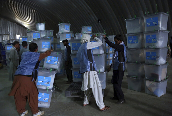FILE - in this Sept. 29, 2019 file photo, Afghan election workers stack ballot boxes at the warehouse of Afghanistan's Independent Election Commission, in Kabul, Afghanistan. Afghan officials have set a new date for announcing the result of last month's presidential election, after several delays. Hawa Alam Nuristani, head of the Independent Election Commission, said Sunday Oct. 27, 2019, that preliminary results will be announced on Nov. 14. (AP Photo/Rahmat Gul, File)