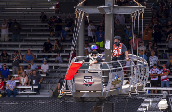 A NASCAR official holds a red flag as the race is stopped while repairs are made to the course during a NASCAR Cup Series auto race at Indianapolis Motor Speedway, Sunday, Aug. 15, 2021, in Indianapolis. (AP Photo/Doug McSchooler)