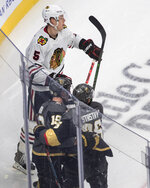 Chicago Blackhawks' Connor Murphy (5) skates by as Vegas Golden Knights' Reilly Smith (19) and Paul Stastny (26) celebrate a goal during the third period in Game 1 of an NHL hockey Stanley Cup first-round playoff series, Tuesday, Aug. 11, 2020, in Edmonton, Alberta. (Jason Franson/The Canadian Press via AP)