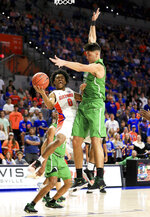 Florida guard Ques Glover (0) is defended by Marshall center Goran Miladinovic (50) during the first half of an NCAA college basketball game Friday, Nov. 29, 2019, in Gainesville, Fla. (AP Photo/Matt Stamey)
