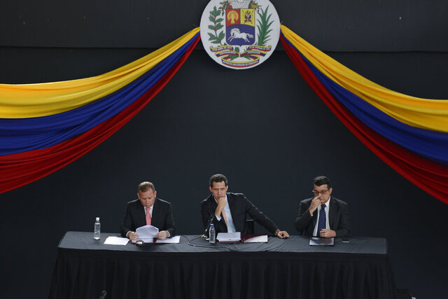 Opposition leader Juan Guaido, center, sits with fellow lawmakers Juan Pablo Guanipa, left, and Carlos Eduardo Berrizbeitia as they hold a session at a theater in the El Hatillo neighborhood after their vehicles were attacked by government supporters while driving to the National Assembly in downtown Caracas, Venezuela, Wednesday, Jan. 15, 2020. It's the second time this month that lawmakers have been barred from from the building that houses the only branch of government out of control of President Nicolas Maduro's government. (AP Photo/Matias Delacroix)