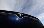 FILE - In this Nov. 10, 2019, file photo the company logo shines off the grille of an unsold 2020 Model X at a Tesla dealership in Littleton, Colo. Tesla reports financial results on Wednesday, Jan. 29, 2020. (AP Photo/David Zalubowski, File)