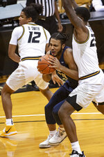 Oral Roberts' Kevin Obanor, center, fights his way between Missouri's Dru Smith, left, and Jeremiah Tilmon during the first half of an NCAA college basketball game Wednesday, Nov. 25, 2020, in Columbia, Mo. (AP Photo/L.G. Patterson)