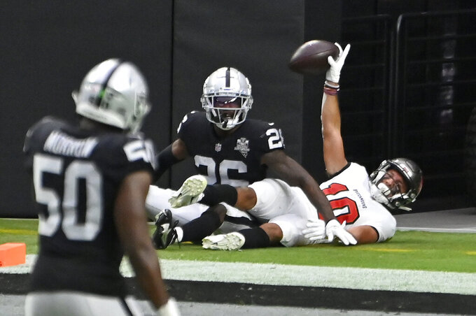 Tampa Bay Buccaneers wide receiver Scott Miller (10) celebrates after scoring a touchdown over Las Vegas Raiders cornerback Nevin Lawson (26) during the first half of an NFL football game, Sunday, Oct. 25, 2020, in Las Vegas. (AP Photo/David Becker)