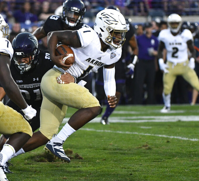 Akron quarterback Kato Nelson (1 runs against Northwestern defensive lineman Samdup Miller (91) during the first half of an NCAA college football game in Evanston, Ill., Saturday, Sept. 15, 2018. (AP Photo/Matt Marton)