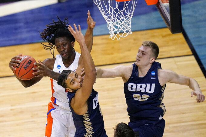 Florida forward Anthony Duruji, left, fights for a rebound with Oral Roberts forward Kevin Obanor, center, and forward Francis Lacis, right, during the first half of a college basketball game in the second round of the NCAA tournament at Indiana Farmers Coliseum, Sunday, March 21, 2021 in Indianapolis. (AP Photo/AJ Mast)