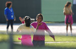 Two girls give high-fives as they play soccer at the Homestead Temporary Shelter for Unaccompanied Children, Tuesday, Feb. 19, 2019, in Homestead, Fla. (AP Photo/Wilfredo Lee)