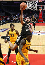 Nevada forward Caleb Martin, center, shoots as Arizona State forwards Romello White, left and Zylan Cheatham defend during the second half of an NCAA college basketball game at the Basketball Hall of Fame Classic on Friday, Dec. 7, 2018, in Los Angeles. (AP Photo/Mark J. Terrill)