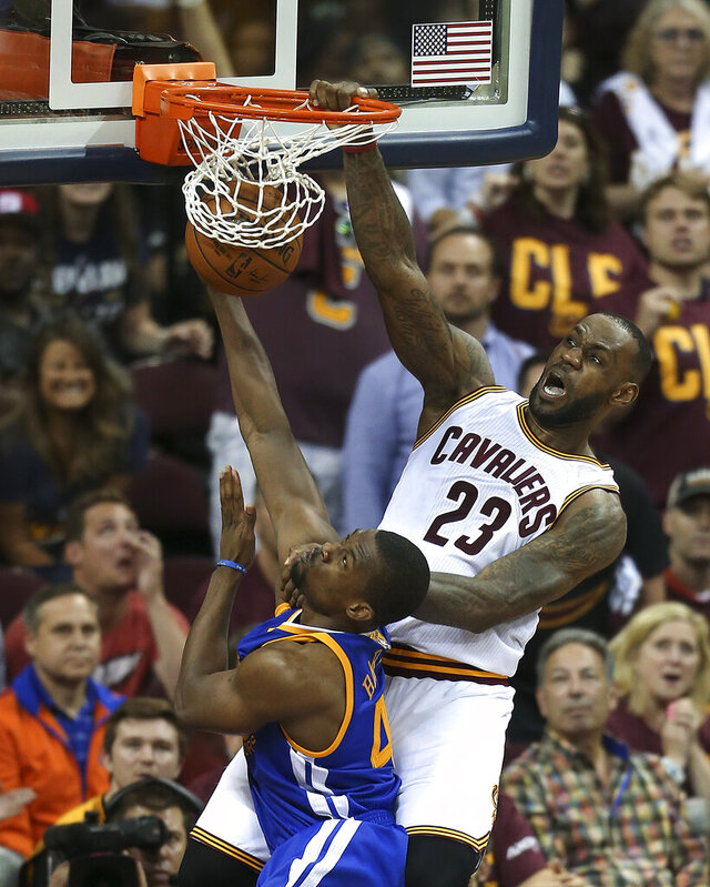FILE - In this June 10, 2016, file photo, Cleveland Cavaliers forward LeBron James (23) dunks on Golden State Warriors forward Harrison Barnes (40) during the second half of Game 4 of basketball's NBA Finals in Cleveland. ESPN will air NBA doubleheaders on Wednesday nights during April showcasing key NBA Finals games. (AP Photo/Ron Schwane, File)