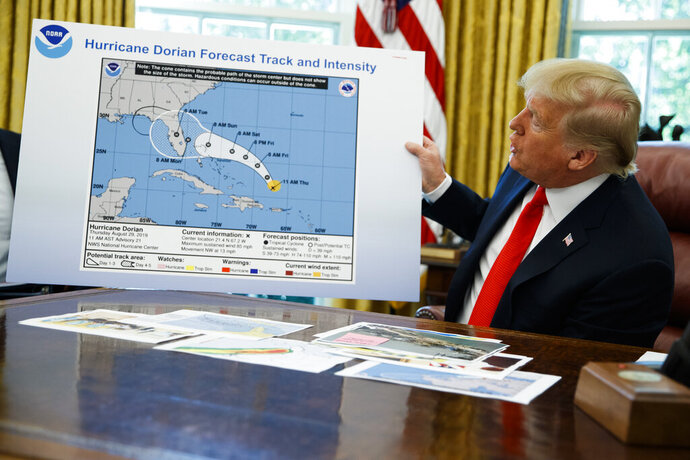 """FILE - In this Wednesday, Sept. 4, 2019 file photo, President Donald Trump holds a chart as he talks with reporters after receiving a briefing on Hurricane Dorian in the Oval Office of the White House in Washington. A report from the National Academy of Public Administration released on Monday, June 15, 2020 says that NOAA's acting chief Neil Jacobs and its then-communications director, Julie Kay Roberts, twice breached the agency's rules designed to protect scientists and their work from political interference, putting out a press statement that """"did not follow NOAA's normal proves and appear to be the result of strong external pressure."""" (AP Photo/Evan Vucci)"""