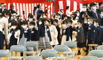 First-year pupils wearing face mask attend their entrance ceremony amid concern over the spread of coronavirus, at an elementary school in Sapporo, northern Japan, Monday, April 6, 2020. In Japan, reports say Prime Minister Shinzo Abe plans to declare an emergency in Tokyo and other cities Tuesday. (Kyodo News via AP)