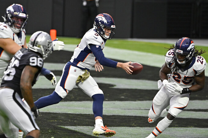 Denver Broncos quarterback Drew Lock (3) looks to handoff the ball against the Las Vegas Raiders during the first half of an NFL football game, Sunday, Nov. 15, 2020, in Las Vegas. (AP Photo/David Becker)