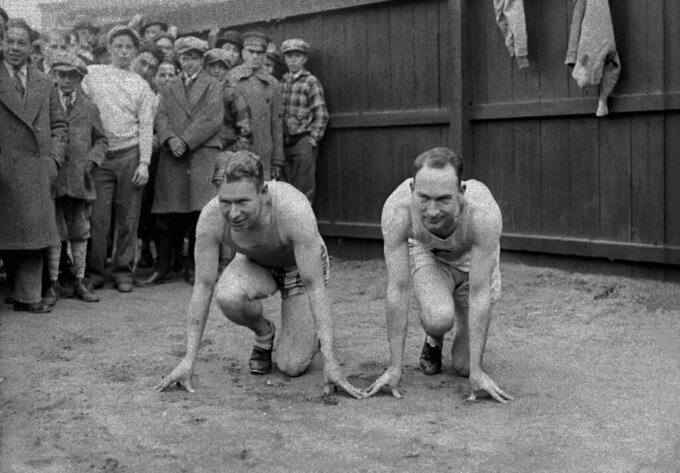 "FILE - In this March 29, 1928, file photo, American sprinters and Olympic champions Jackson Scholz, left, and Charles ""Charley"" Paddock pose together in their starting positions at New York's Columbia University. (AP Photo/File)"