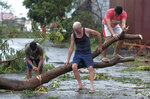 Men cut down a tree that fell due to strong winds as Typhoon Kammuri slammed Legazpi city, Albay province, southeast of Manila, Philippines on Tuesday, Dec. 3, 2019. Typhoon Kammuri barreled across the Philippine archipelago with fierce rain and wind Tuesday, leaving at least four people dead, forcing tens of thousands of villagers to abandon high-risk communities and prompting officials to shut Manila's international airport.  (AP Photo)