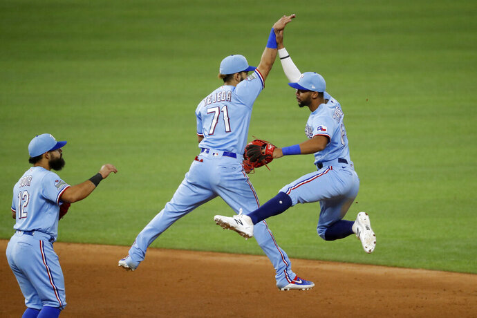 Texas Rangers shortstop Anderson Tejeda (71) celebrates with center fielder Leody Taveras, right, while second baseman Rougned Odor, left, looks on after a baseball game against the Houston Astros in Arlington, Texas, Sunday, Sept. 27, 2020. Texas beat Houston 8-4. (AP Photo/Roger Steinman)