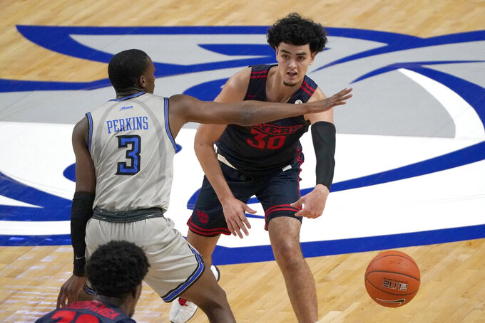 Dayton's Mustapha Amzil (30) passes around Saint Louis' Javonte Perkins (3) during the first half of an NCAA college basketball game Tuesday, Jan. 26, 2021, in St. Louis. (AP Photo/Jeff Roberson)