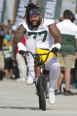 FILE - In this Thursday, July 25, 2019 file photo, Green Bay Packers' Billy Turner rides a bike to NFL football training camp in Green Bay, Wis. Green Bay Packers right guard William