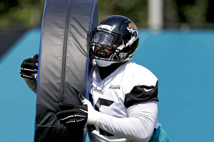 FILE - In this June 4, 2018, file photo, Jacksonville Jaguars defensive tackle Abry Jones performs a drill during an NFL football practice in Jacksonville, Fla. As the league celebrates its 100th season, it continues to expand its foreign footprint with five international games in 2019. Abry Jones has made six trips to London in as many seasons. (AP Photo/John Raoux, File)