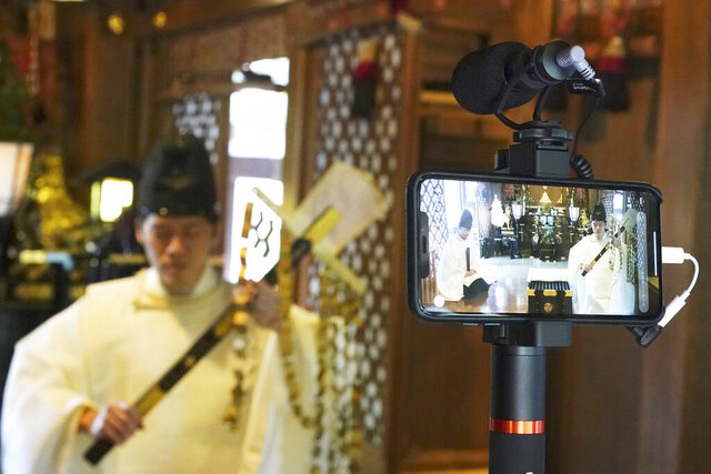 In this May 8, 2020, photo, Ryoki Ono, head priest, performs a livestream prayer during a 10-day trial of