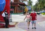 Tourists walk past restaurants and shops along an empty sidewalk in Cancun, Mexico, Saturday, June 13, 2020. In Quintana Roo state, where Cancun is located, tourism is the only industry there is, and Cancun is the only major Mexican resort to reopen so far. (AP Photo/Victor Ruiz)