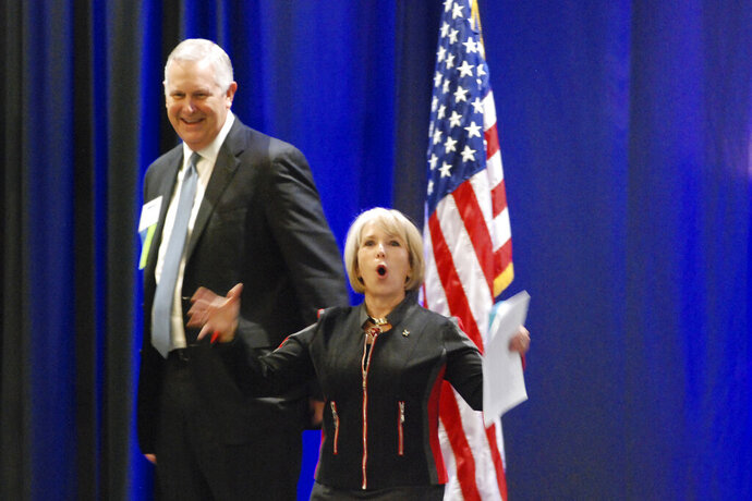 New Mexico Gov. Michelle Lujan Grisham, foreground, gestures in front of Scott Kidwell, chairman of the New Mexico Oil and Gas Association, at the association's annual meeting in Santa Fe, N.M., Tuesday, Oct. 8, 2019. Lujan Grisham praised the oil industry's role in underwriting public education and solicited its help in developing new state regulations for methane emissions. (AP Photo/Morgan Lee)