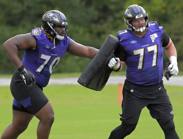 FILE - In this Sept. 1, 2020, file photo, Baltimore Ravens guard D.J. Fluker (70) runs behind guard Bradley Bozeman (77) during NFL football team practice at the Ravens' facility in Owings Mill, Md. The mother of Fluker's child faces a misdemeanor kidnapping charge after being accused of refusing to give their child back to Fluker after a supervised visit. Kimberly Davis was arrested and charged Tuesday, Sept. 22, 2020, by Baltimore County police, news outlets reported. (Karl Merton Ferron/The Baltimore Sun via AP, File)