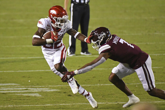 Arkansas running back Trelon Smith (22) looks for room past Mississippi State safety Marcus Murphy (7) during the first half of an NCAA college football game in Starkville, Miss., Saturday, Oct. 3, 2020. (AP Photo/Thomas Graning)