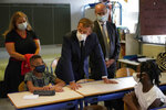 French President Emmanuel Macron, center, flanked with French Education, Youth and Sports Minister Jean-Michel Blanquer, right, looks on during a visit at Bouge primary school in Malpasse district of Marseille, southern France, Thursday Sept. 2, 2021 as twelve million children in France went back to school Thursday for the new academic year, wearing face masks as part of rules aimed at slowing down the spreading of the virus in the country. French President Emmanuel Macron, accompanied by several ministers, is on a three-day visit to the southern city of Marseille to address security, education and housing issues. (AP Photo/Daniel Cole, pool)