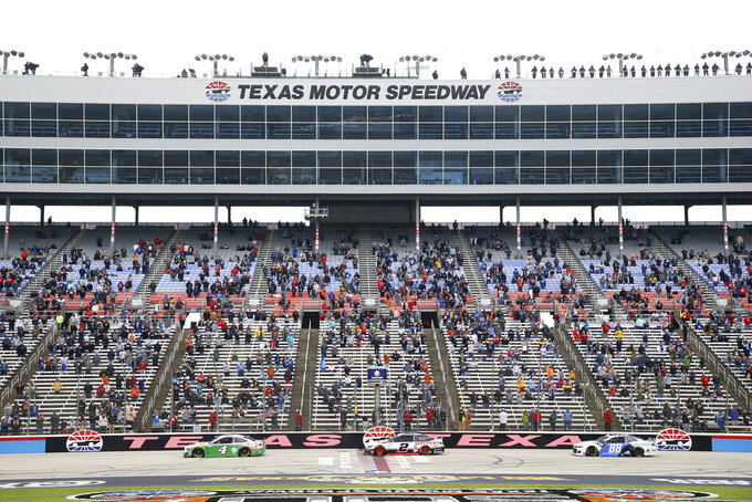 Kevin Harvick (4), Brad Keselowski (2) and Alex Bowman (88) pass the grandstand on the front stretch of a NASCAR Cup Series auto race at Texas Motor Speedway in Fort Worth, Texas, Sunday, Oct. 25, 2020. (AP Photo/Richard W. Rodriguez)