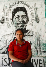 Liliana Velazquez poses for a photo in front of a mural depicting her murdered husband and community activist Samir Flores in Amilcingo, Morelos state, Mexico, Saturday, Feb. 22, 2020. Last year, Flores who had drummed up opposition against a power plant being built in the area was shot dead outside his home in the town of Amilcingo. (AP Photo/Eduardo Verdugo)