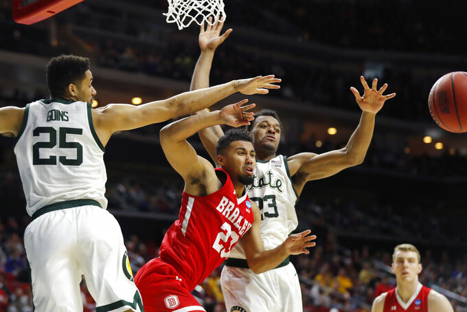 Bradley guard Dwayne Lautier-Ogunleye, center, passes between Michigan State's Kenny Goins, left, and Xavier Tillman, right, during a first round men's college basketball game in the NCAA Tournament, Thursday, March 21, 2019, in Des Moines, Iowa. (AP Photo/Charlie Neibergall)