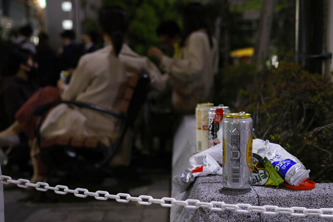Cans and snacks packages are left as people drink at a park in Tokyo on April 21, 2021. Trains packed with commuters returning to work after a weeklong national holiday. Frustrated young people drinking in the streets because bars are closed. Protests planned over a possible visit by the Olympics chief. As the coronavirus spreads in Japan ahead of the Tokyo Olympics starting in 11 weeks, one of the world's least vaccinated nations is showing signs of strain, both societal and political. (Kyodo News via AP)