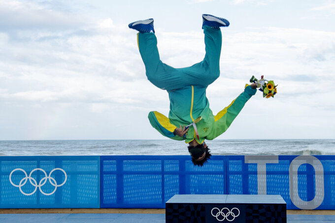 Brazil's Italo Ferreira, holding his gold medal, celebrates on the podium in the men's surfing competition at the 2020 Summer Olympics, Tuesday, July 27, 2021, at Tsurigasaki beach in Ichinomiya, Japan. (Olivier Morin/Pool Photo via AP)