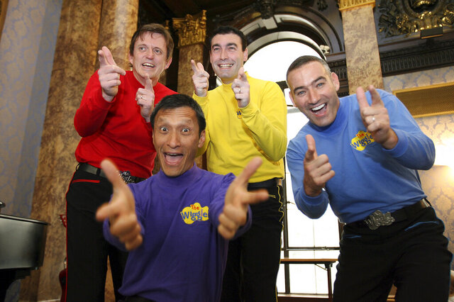 FILE - In this June 28, 2006 file photo, Australian children's entertainers The Wiggles, Murray Cook (Red Wiggle), Greg Page (Yellow Wiggle), Jeff Fatt (Purple Wiggle), and Anthony Field (Blue Wiggle) make a special appearance at the Australian High Commission in London at the start of their UK tour. Page, one of the original members of the popular Australian children's band has been hospitalized after collapsing during a wildfire relief concert.  Page fell as he left a stage in New South Wales and went into cardiac arrest. He had been performing with the other original bandmates to raise money for the Red Cross and the wildlife rescue group WIRE.  (AP Photo/Christopher Pledger, File)