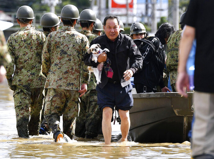 An evacuee with a dog is rescued by Self-Defense force members as the city is hit by Typhoon Hagibis, in Motomiya, Fukushima prefecture, northern Japan, Sunday, Oct. 13, 2019. Rescue efforts for people stranded in flooded areas are in full force after a powerful typhoon dashed heavy rainfall and winds through a widespread area of Japan, including Tokyo.(Kyodo News via AP)