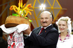 FILE In this file photo taken on Friday, Sept. 21, 2012, Belarusian President Alexander Lukashenko receives bread and salt during the Dazhynki harvest festival in the town of Gorki, some 270 km (168 miles) east of Minsk, Belarus. Belarus' authoritarian President Alexander  Lukashenko faces a perfect storm as he seeks a sixth term in the election held Sunday, Aug. 9, 2020 after 26 years in office. Mounting public discontent over the worsening economy and his government's bungled handling of the coronavirus pandemic has fueled the largest opposition rallies since the Soviet collapse. (AP Photo/Vasily Fedosenko, Pool)