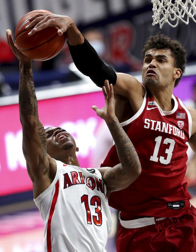 Stanford forward Oscar da Silva, right, blocks a shot by Arizona guard James Akinjo (13) during the first half of an NCAA college basketball game in Tucson, Ariz., Thursday, Jan. 28, 2021. (Kelly Presnell/Arizona Daily Star via AP)