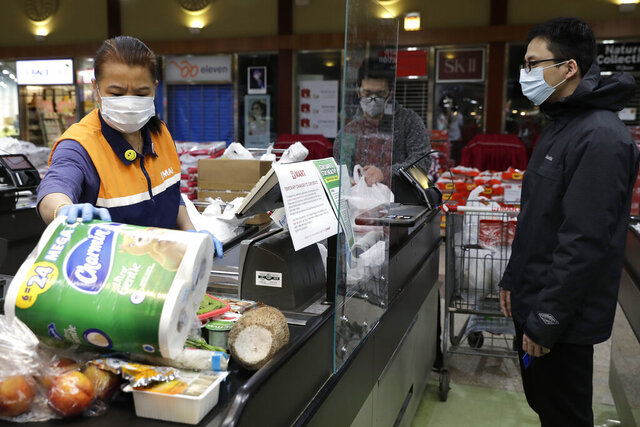 A cashier, left, works behind a plexiglass shield at a Super H Mart grocery store in Niles, Ill., Thursday, March 26, 2020. Local grocery stores are installing plexiglass shields in the checkout aisle as a coronavirus precaution. (AP Photo/Nam Y. Huh)