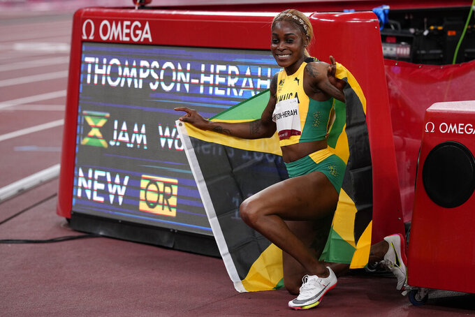 Elaine Thompson-Herah of Jamaica, poses for photographs by the clock after winning the women's 100-meters final at the 2020 Summer Olympics, Saturday, July 31, 2021, in Tokyo. (AP Photo/David J. Phillip)