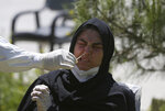FILE - In this May 18, 2020, file, photo, an Afghan lab technician takes a sample with a swab to test a woman for the coronavirus at the Afghan-Japan Communicable Disease Hospital, Kabul's main facility for coronavirus testing and treatment, in Kabul, Afghanistan. A prominent international aid organization warned Tuesday, June 2, 2020 that Afghanistan is on the brink of a humanitarian disaster because the government is unable to test at least 80% of possible coronavirus cases.  (AP Photo/Rahmat Gul, File)