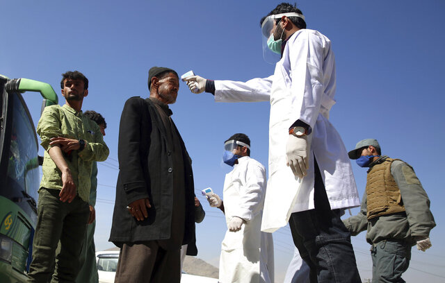 FILE - In this Sunday, March 22, 2020 file photo, health workers measure the temperature of Afghan passengers in an effort to prevent the spread of the coronavirus, as they enter Kabul trough Kabul's western entrance gate, in the Paghman district of Kabul, Afghanistan. An international aid group says Friday, May 22, 2020 that some 661,000 people in 19 countries have been displaced by armed conflict in the two months since the U.N. secretary general called for a global cease-fire to help curb the coronavirus pandemic. The Norwegian Refugee Council says in a report Friday that the bulk of the newly displaced were in the Democratic Republic of Congo, but that large numbers were also uprooted in Yemen, Afghanistan, Chad and Niger. (AP Photo/Rahmat Gul, File)