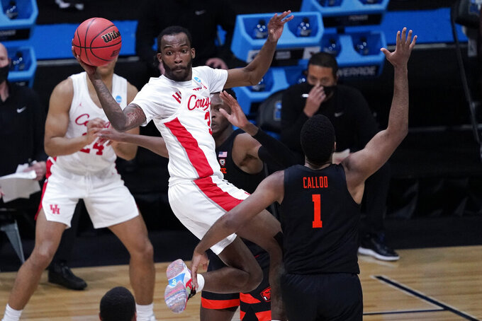 Houston guard DeJon Jarreau (3) passes over Oregon State forward Maurice Calloo (1) during the first half of an Elite 8 game in the NCAA men's college basketball tournament at Lucas Oil Stadium, Monday, March 29, 2021, in Indianapolis. (AP Photo/Darron Cummings)