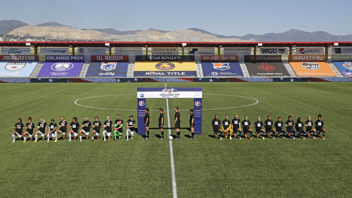 Players for the Portland Thorns, left, and the North Carolina Courage kneel during the national anthem before the start of their NWSL Challenge Cup soccer match at Zions Bank Stadium Saturday, June 27, 2020, in Herriman, Utah. (AP Photo/Rick Bowmer)