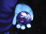 FILE- In a Sept. 4, 2018 file photo, Erik Rintamaki of Brimley, Mich., holds a sodalite rock gathered from the shore of Lake Superior and illuminated by an ultraviolet light. Rintamaki collects and sells the rocks, which he's named