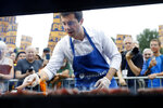 Democratic presidential candidate Pete Buttigieg works the grill during the Polk County Democrats Steak Fry, Saturday, Sept. 21, 2019, in Des Moines, Iowa. (AP Photo/Charlie Neibergall)