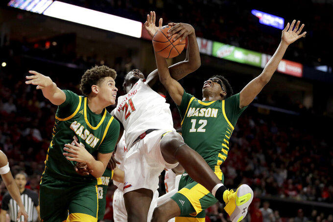 Maryland forward Makhi Mitchell (21) goes up for a rebound against George Mason forwards Josh Oduro, left, and AJ Wilson (12) during the second half of an NCAA college basketball game Friday, Nov. 22, 2019, in College Park, Md. Maryland won 86-63. (AP Photo/Julio Cortez)