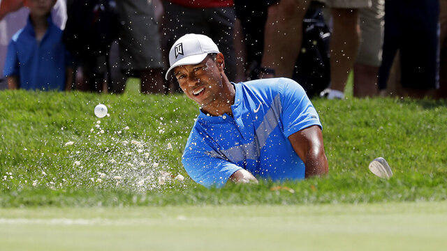 FILE - In this Thursday, Aug. 15, 2019 file photo, Tiger Woods hits from a sand trap on the fourth hole during the first round of the BMW Championship golf tournament at Medinah Country Club in Medinah, Ill. Woods is in the Bahamas this week as a player and a host, and in Australia next week as a player and Presidents Cup captain. (AP Photo/Nam Y. Huh, File)